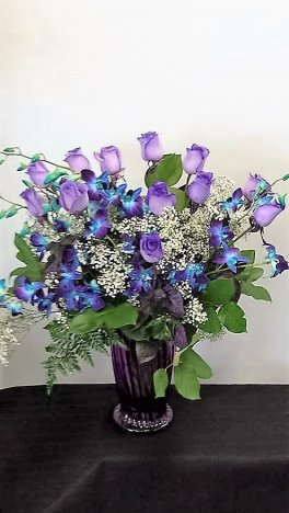 A purple roses blue orchids vase flower arrangement