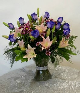 a purple roses with Lilies vase arrangement